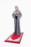 Arab muslim woman praying. On a praying carpet. Isolated on white background Stock Image