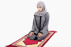 Arab muslim woman praying. On a praying carpet. Isolated on white background Royalty Free Stock Photo