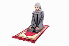 Arab muslim woman praying. On a praying carpet. Isolated on white background Royalty Free Stock Image