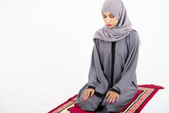 Arab muslim woman praying. On a praying carpet. Isolated on white background Stock Photos
