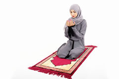 Arab muslim woman praying. On a praying carpet.  on white background Stock Image