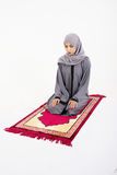Arab muslim woman praying. On a praying carpet.  on white background Royalty Free Stock Image