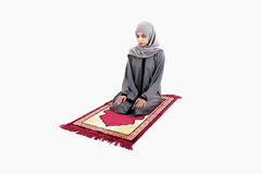 Arab muslim woman praying. On a praying carpet.  on white background Stock Photos
