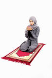 Arab muslim woman praying. On a praying carpet.  on white background Royalty Free Stock Images