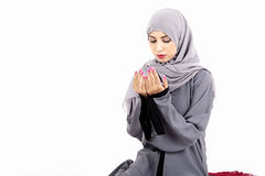 Arab muslim woman praying. On a praying carpet.  on white background Stock Photo