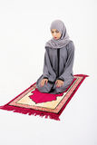 Arab muslim woman praying. On a praying carpet.  on white background Royalty Free Stock Photography