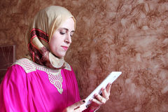 Arab muslim woman with tablet. Photo of arabian egyptian muslim woman looking through tablet Royalty Free Stock Photos
