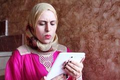 Arab muslim woman with tablet. Photo of arabian egyptian muslim woman looking through tablet Stock Photo