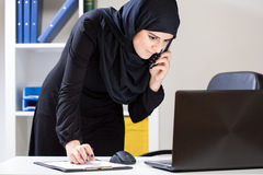 Arab office worker using laptop stock image