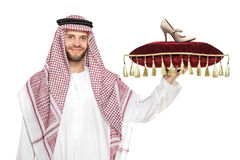 An arab person holding a pillow with a shoe on it royalty free stock photo