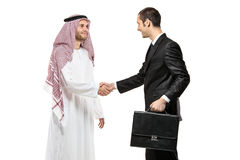 An Arab person shaking hands with a businessman stock photo