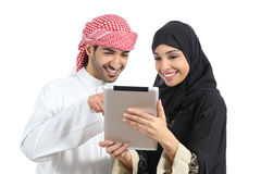 Arab saudi happy couple browsing a tablet reader. Isolated on a white background Royalty Free Stock Image