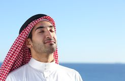 Arab saudi man breathing deep fresh air in the beach. With the ocean and horizon in the background Royalty Free Stock Images