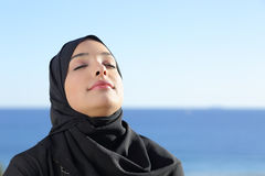 Arab saudi woman breathing deep fresh air in the beach. With the ocean and horizon in the background Royalty Free Stock Photography