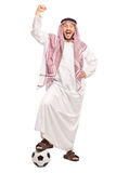 Arab stepping over a football and gesturing happiness Royalty Free Stock Photography