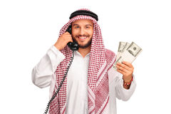Arab talking on a phone and holding money Royalty Free Stock Photos