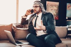 Arab talking on phone and sitting on couch stock photo