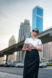 Arab trade. Successful arabic businesswoman standing. In the street in formal attire. Businessman standing near skyscrapers in Dubai downtown in sunglasses Stock Photo