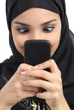 Arab woman addicted to the smartphone. Isolated on a white background Stock Photos