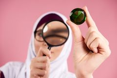 Arab woman in hijab examines precious stone. Through magnifying glass. Isolated on pink background stock photo