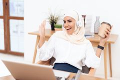 An Arab woman in hijab listens to music on headphones. royalty free stock photo