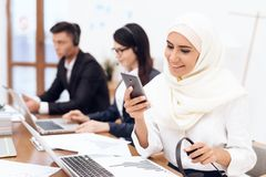An Arab woman in a hijab looks at the phone. An Arab women in a hijab looks at the phone. She is in the office. Her colleagues work nearby Stock Image