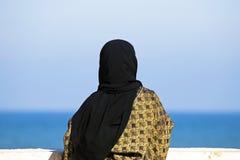Arab woman looking over the ocean Stock Photos
