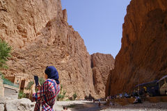 An Arab woman photographed with her phone in the river of The Todra gorges in Morocco. The Todra gorges in Arabic: مضيق تودغا, Maḍīq Tūdgha are a Royalty Free Stock Images