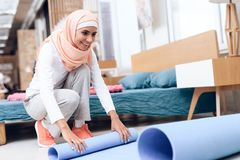 Arab woman preparing a mat to do gymnastics in the bedroom. stock images
