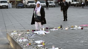 Arab woman reading messages around monument - French city after attacks stock video