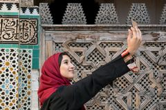 Arab woman in traditional clothing taking selfie in front of the. Arab woman in traditional clothing taking selfie with mobile phone in front of the wall with Stock Image
