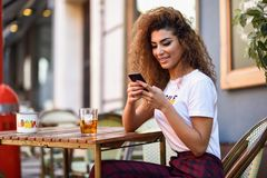 Arab woman in an urban bar at her smartphone. Young arabic woman smiling and sitting in an urban bar in the street looking at her smartphone. Arab girl in Stock Photo