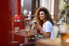 Arab woman in an urban bar at her smartphone. Young arabic woman smiling and sitting in an urban bar in the street looking at her smartphone. Arab girl in Royalty Free Stock Photos