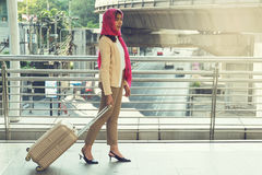 Arab woman walking carrying a suitcase Royalty Free Stock Images