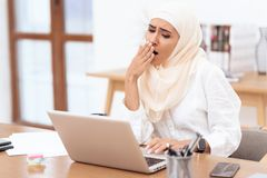 Arab woman wearing a headscarf sitting tired at work. stock photo