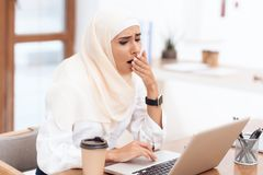 Arab woman wearing a headscarf sitting tired at work. stock images