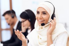 An Arab woman works in a call center. Arabian works at office. Stock Photos