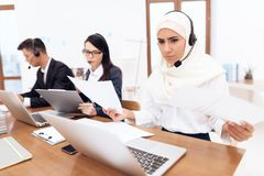 An Arab woman works in a call center. An Arab women works in a call center. She`s an operator. Her colleagues work nearby stock photos