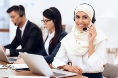 An Arab woman works in a call center. An Arab women works in a call center. She`s an operator. Her colleagues work nearby royalty free stock image