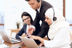 An Arab woman works in a call center. An Arab women works in a call center. She`s an operator. Her colleagues work nearby stock images