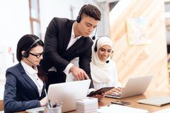 An Arab woman works in a call center. An Arab women works in a call center. She`s an operator. Her colleagues work nearby royalty free stock photo