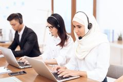An Arab woman works in a call center. An Arab women works in a call center. She`s an operator. Her colleagues work nearby royalty free stock images