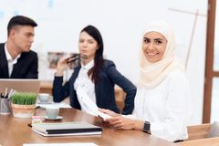 The Arab woman in hijab works in the office together with her colleagues. royalty free stock image