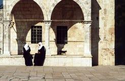 Arab women sit at the wall Royalty Free Stock Photos