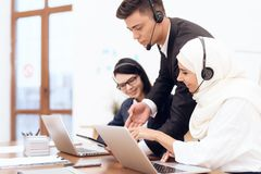 An Arab woman works in a call center. An Arab women works in a call center. She`s an operator. Her colleagues work nearby stock image