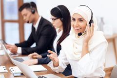 An Arab woman works in a call center. An Arab women works in a call center. She`s an operator. Her colleagues work nearby royalty free stock photography