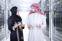 Arab workers discussing in server room. Picture of two Arabian businespeople discussing together in the server room Royalty Free Stock Photography