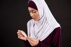 Arab worried woman in hijab holds pregnancy test stock photos