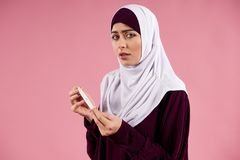 Arab worried woman in hijab holds pregnancy test stock images