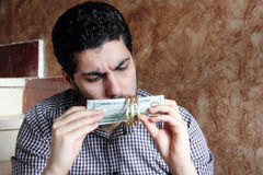 Arab young businessman with dollar bills money and gold jewelry. Arab young muslim business man feeling confused with dollar bills and gold jewelry in his hands Royalty Free Stock Image
